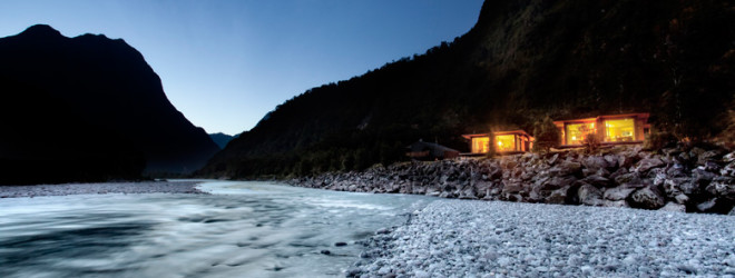 Beautiful picture of river with two lit up cabins at night