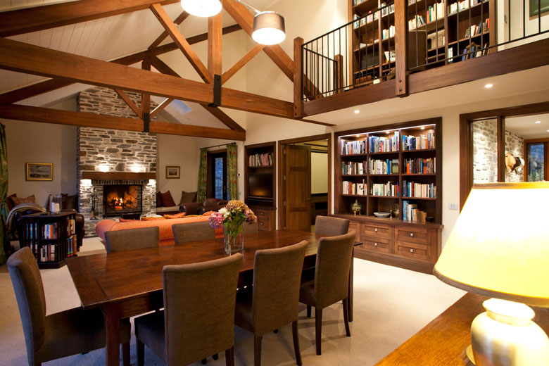 Dining table overlooking open fire, book case and upstairs landing