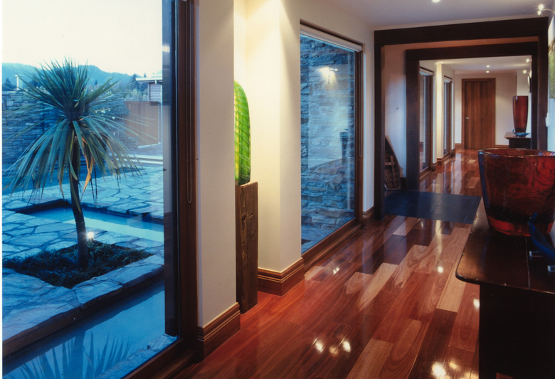 Polished wooden floored hallway with a view to the pool