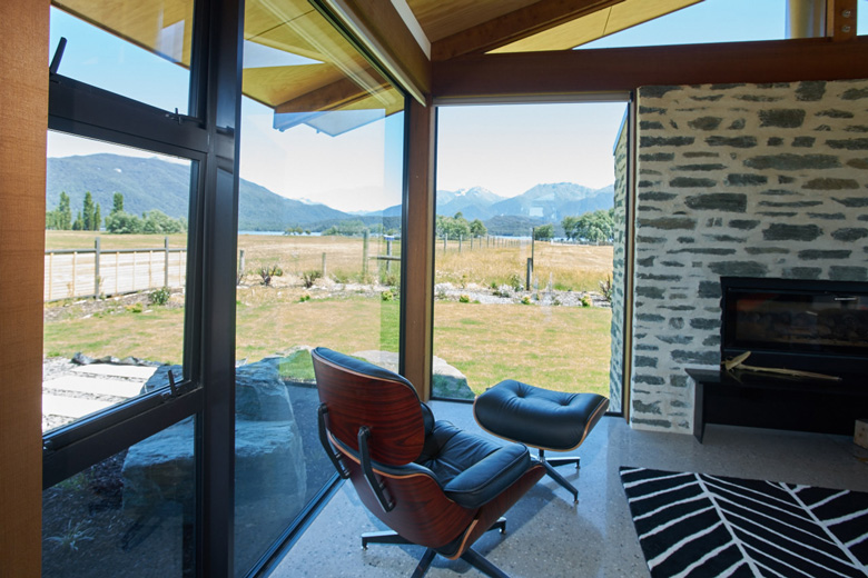 Eames chair by fireplace with view out the window