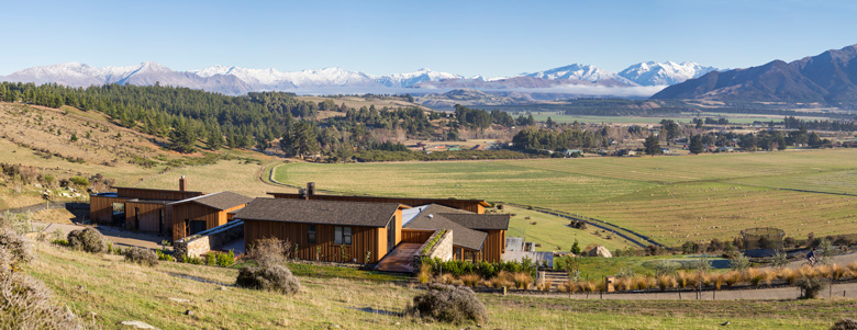 Panoramic photo of house looking over fields and mountains