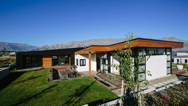 Image of house and lawn with mountains in background